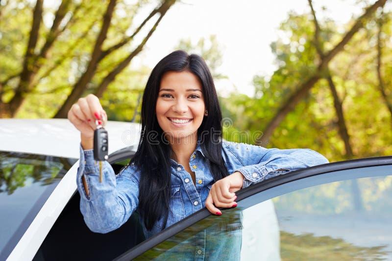 Lycklig kvinnachaufför med biltangenter royaltyfri bild