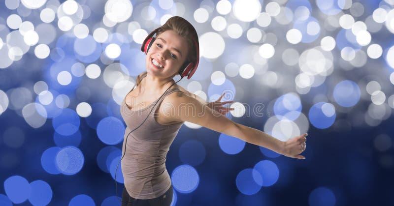 Lycklig kvinnadans, medan lyssna till musik på hörlurar mot bokeh royaltyfri bild