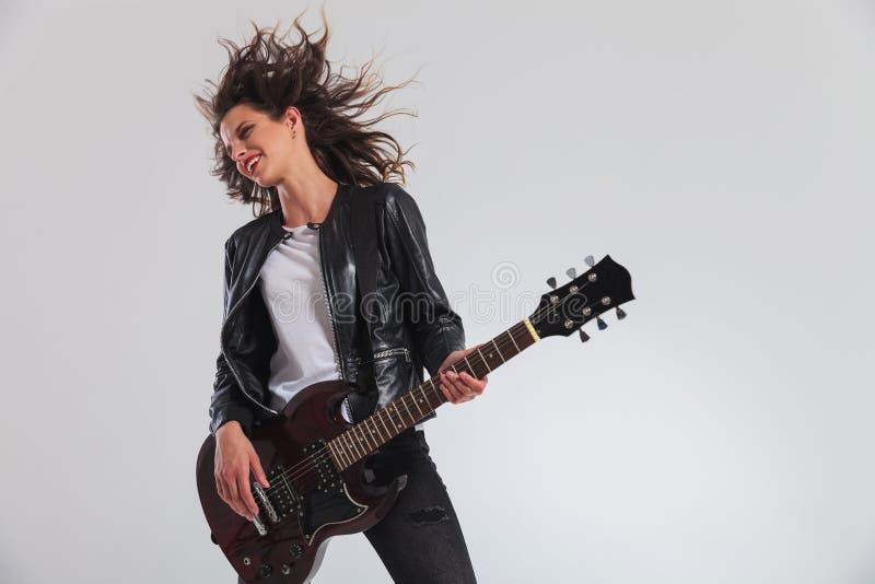 Lycklig kvinnagitarrist för head dängande som spelar gitarren arkivfoton