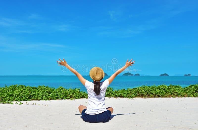 Lycklig kvinnahandelsresande som kopplar av på en perfekt strand royaltyfri fotografi