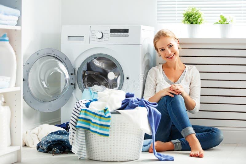 Lycklig kvinnahemmafru i tvättstugan nära tvagningmachien fotografering för bildbyråer
