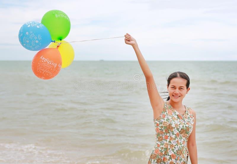 Lycklig kvinnainnehavballong på stranden på semester Den lyckliga mannen tycker om p? ferier p? havet royaltyfri foto
