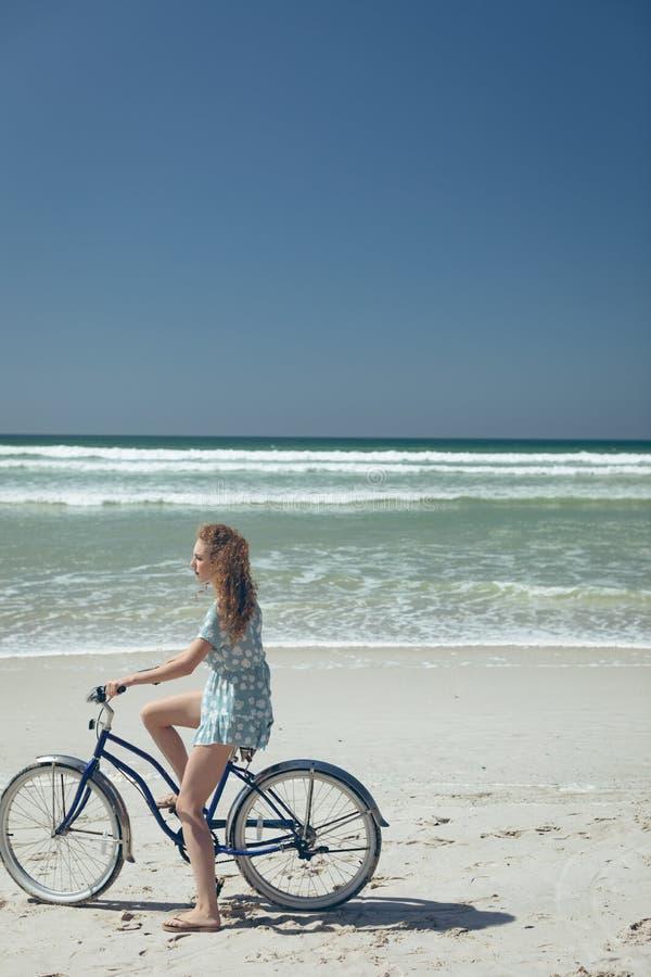Lycklig kvinnainnehavcykel på stranden på en solig dag arkivfoton
