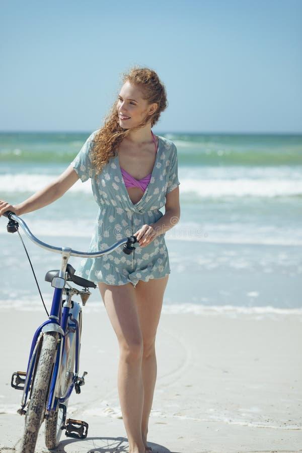 Lycklig kvinnainnehavcykel på stranden royaltyfri bild