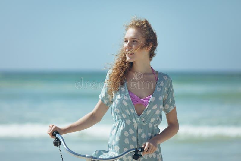 Lycklig kvinnainnehavcykel på stranden arkivfoton
