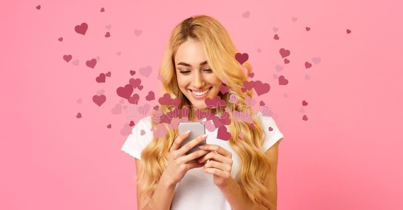 Lycklig kvinnainnehavmobiltelefon med många hjärtor arkivbild