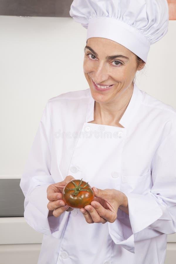 Lycklig kvinnakock med tomaten fotografering för bildbyråer