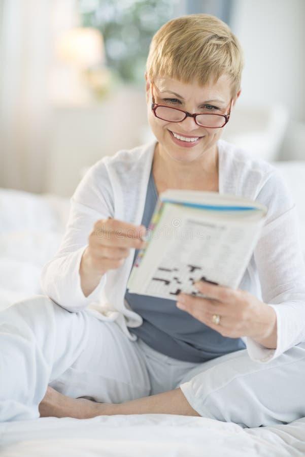 Lycklig kvinnaläsebok på säng arkivbild