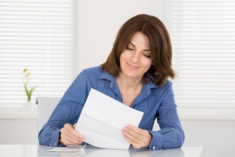Lycklig kvinnaläsningbokstav royaltyfri bild