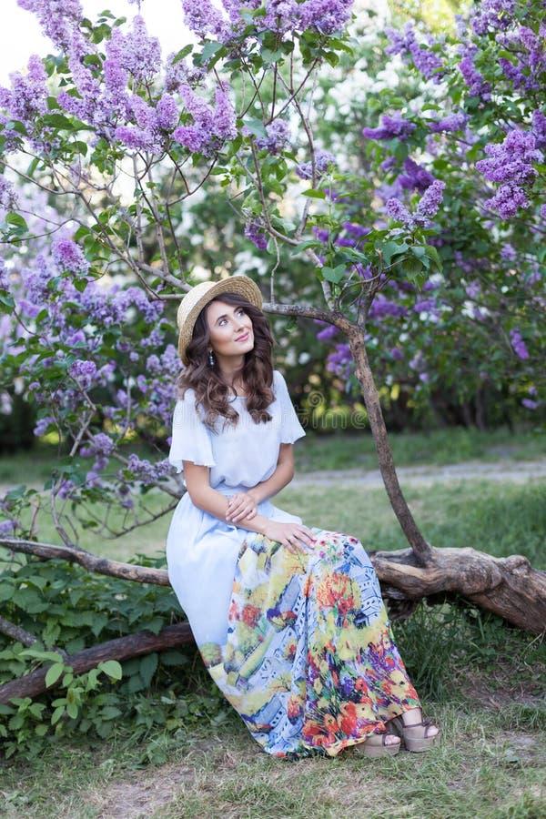Lycklig kvinnalivstil, härlig avkopplad flicka i en sugrörhatt i en lång tappningklänning, lila blommor i strålarna av en mjuk in fotografering för bildbyråer