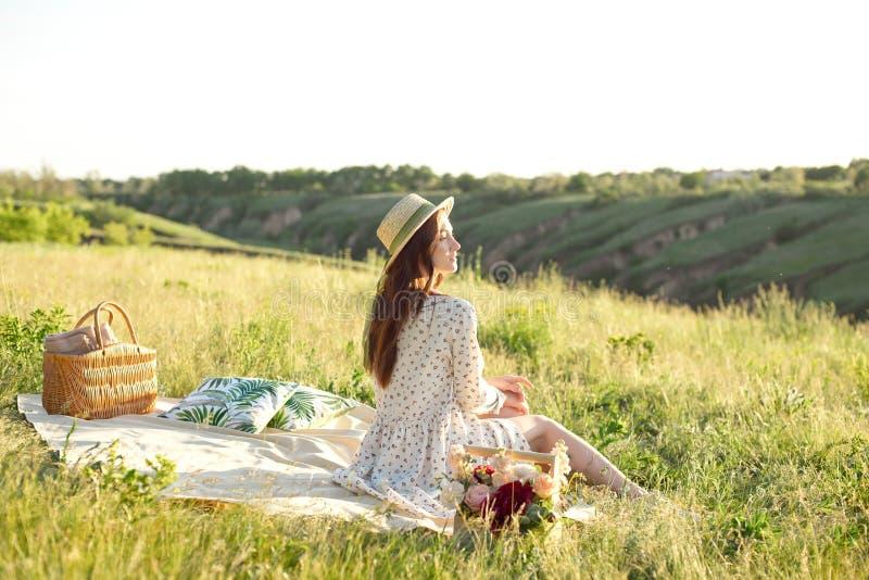Lycklig kvinnalivstil, h?rlig avkopplad flicka i en sugr?rhatt p? blommorna f?r naturpicknickkorg i str?larna av fotografering för bildbyråer