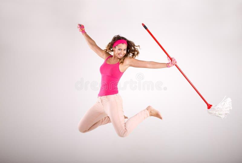 Lycklig kvinnalokalvård och banhoppning med golvmopp arkivfoto