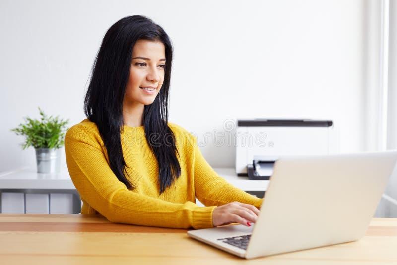 Lycklig kvinnamaskinskrivning på bärbara datorn fotografering för bildbyråer