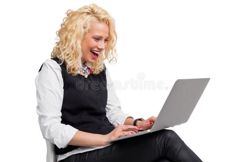 Lycklig kvinnamaskinskrivning på datoren och att skratta royaltyfria foton