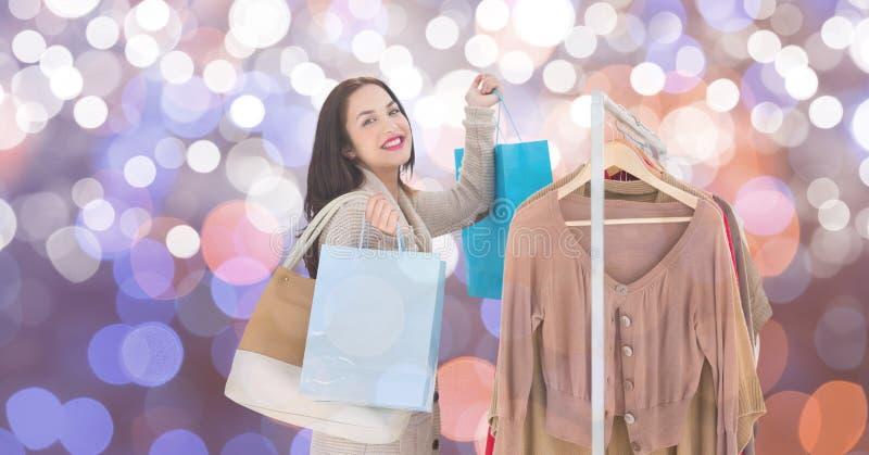 Lycklig kvinnashopping vid kläder rack över suddig bakgrund arkivfoton