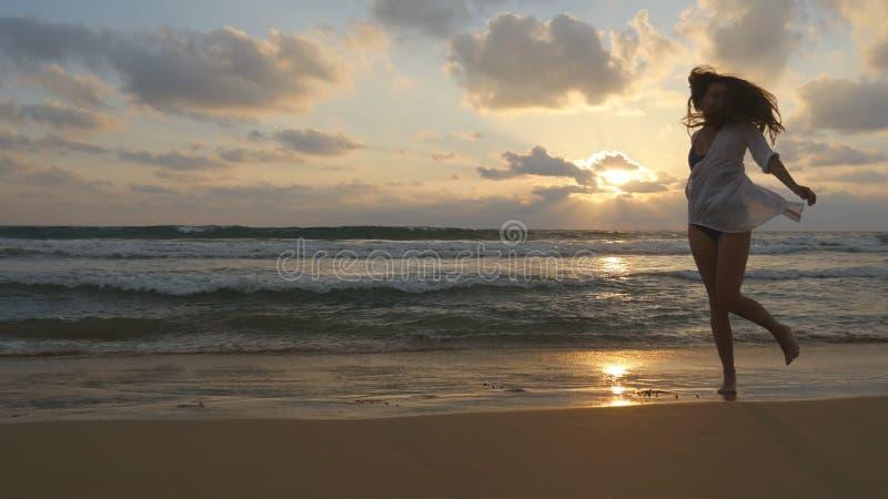 Lycklig kvinnaspring och snurr på stranden nära havet Ung härlig flicka som tycker om liv och har gyckel på havet royaltyfri foto