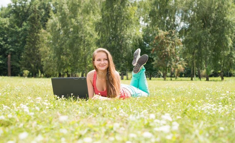 Lycklig kvinnastudent som ligger på gräs med bärbara datorn Lyckad flicka direktanslutet Härlig ung kvinna med anteckningsboken i arkivfoton