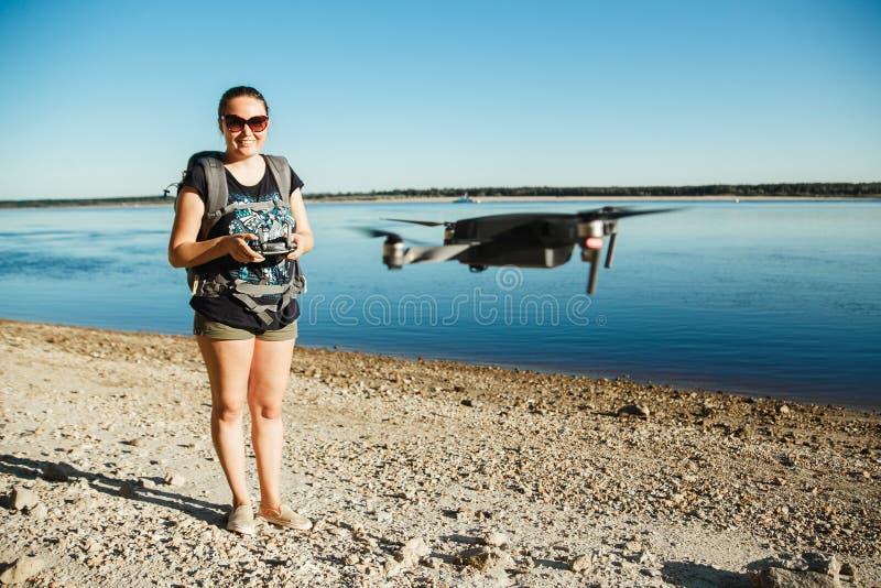 Lycklig kvinnaturist som lanserar surret med fjärrkontrollen arkivfoton