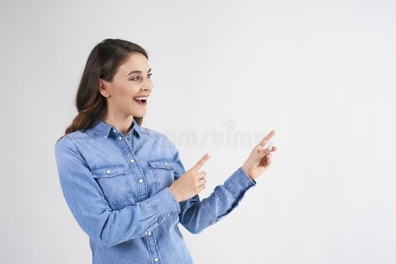 Lycklig kvinnavisning på kopieringsutrymme i studioskott royaltyfri foto