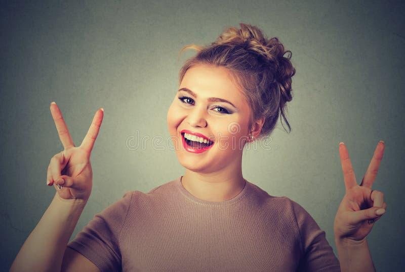 Lycklig kvinnavisningseger eller gest för fredtecken fotografering för bildbyråer