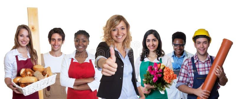 Lycklig kvinnlig affärsdeltagare i utbildning med gruppen av andra internationella lärlingar arkivbild