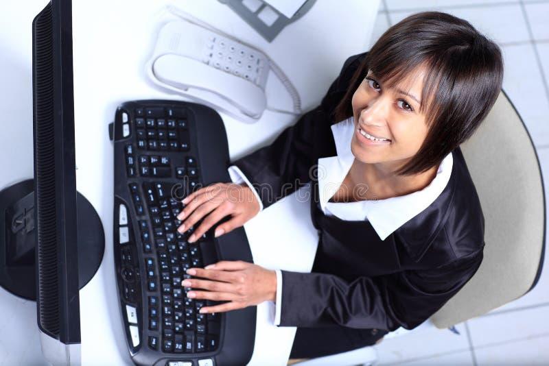 Lycklig kvinnlig affärsledare som arbetar på bärbara datorn. arkivbild