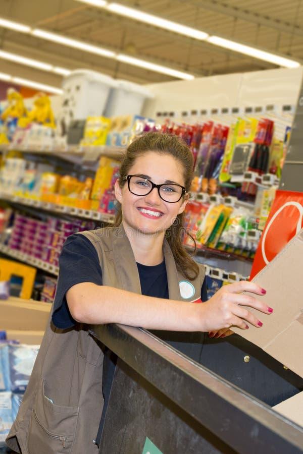 Lycklig kvinnlig arbetare som ordnar papp som förpackar på supermarket royaltyfri fotografi