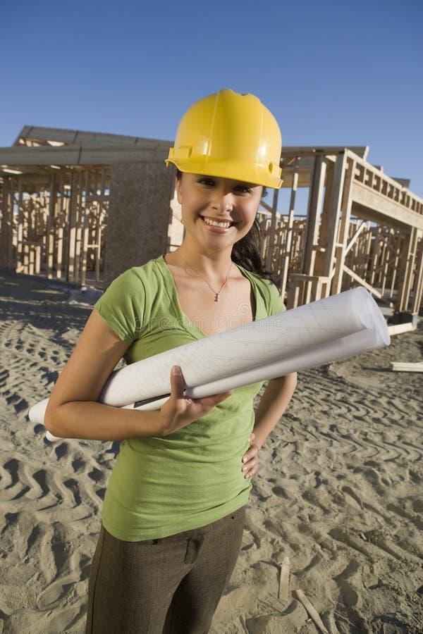 Lycklig kvinnlig arkitekt Holding Blueprint royaltyfri foto