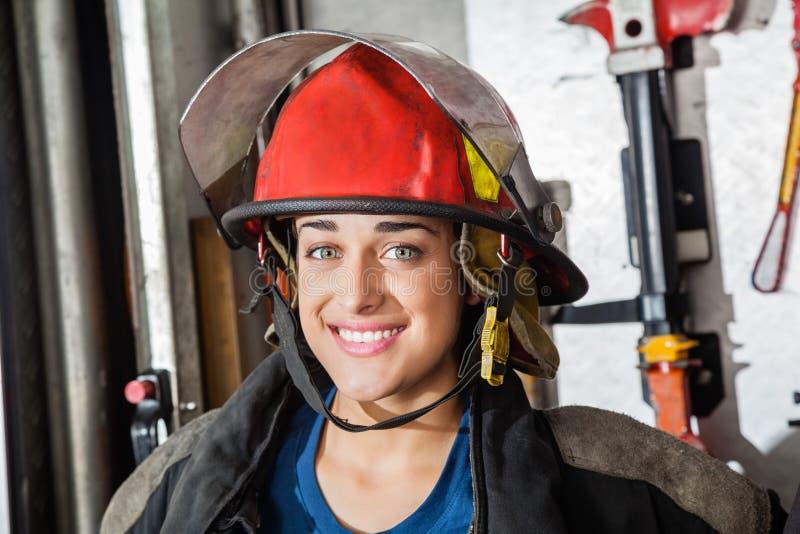Lycklig kvinnlig brandman At Fire Station arkivbilder