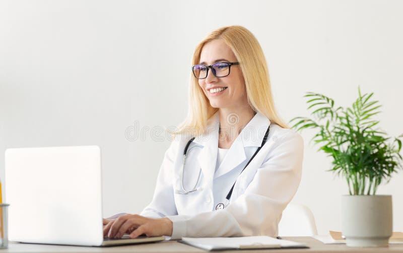 Lycklig kvinnlig dator för doktor Working On Laptop royaltyfria foton