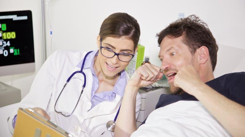 Lycklig kvinnlig doktor och patient i sjukhus som firar botcloseupen royaltyfri foto