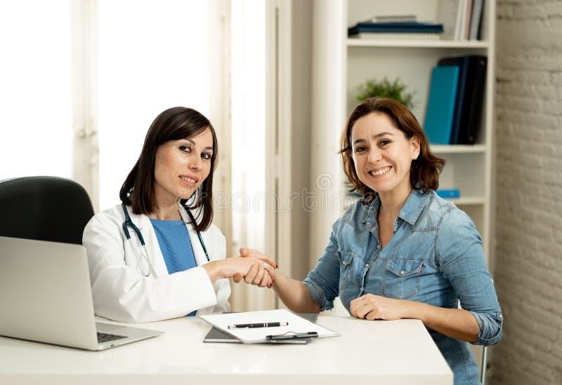 Lycklig kvinnlig doktor och ung le kvinnapatient som skakar händer i klinikkontor arkivfoto