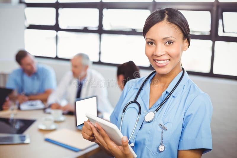 Lycklig kvinnlig doktor som använder den digitala minnestavlan i konferensrum fotografering för bildbyråer