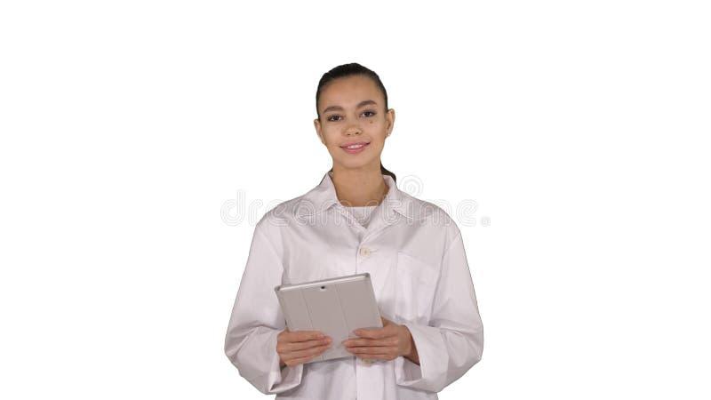 Lycklig kvinnlig doktor som anv?nder minnestavladatoren som nallar sidor p? den p? vit bakgrund royaltyfri foto