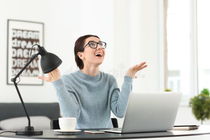 Lycklig kvinnlig freelancer som i regeringsställning arbetar med bärbara datorn arkivfoto