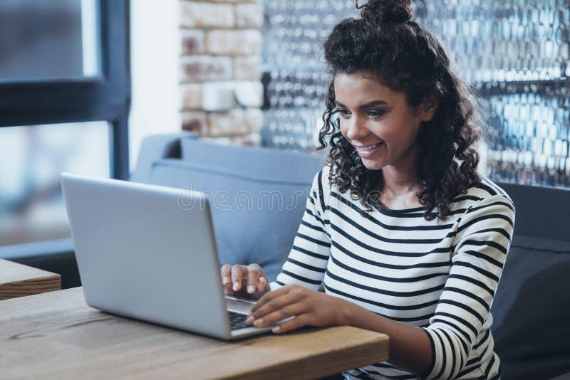 Lycklig kvinnlig freelancer som söker projekt royaltyfri foto