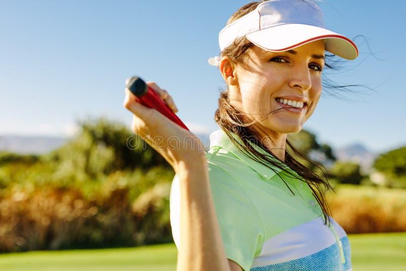 Lycklig kvinnlig golfare med golfklubben på fält royaltyfri foto
