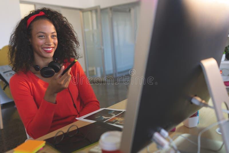 Lycklig kvinnlig grafisk formgivare som arbetar på skrivbordet royaltyfri bild