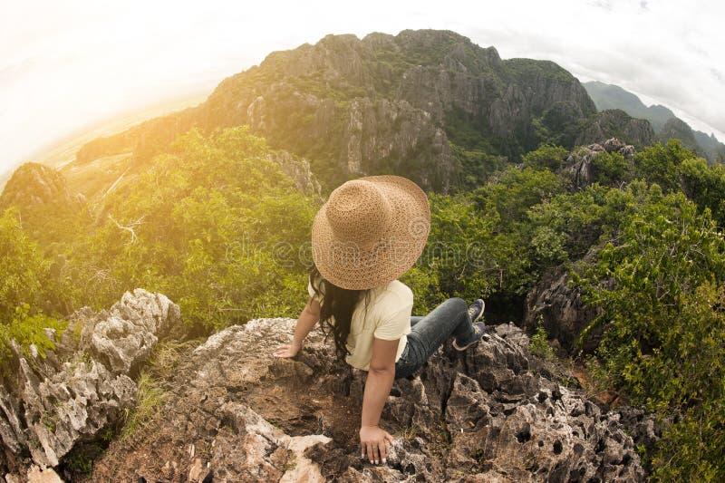 Lycklig kvinnlig handelsresande som överst sitter av ett berg arkivbilder