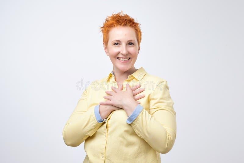 Lycklig kvinnlig i positiva sinnesrörelser för gul skjortavisning, når att ha mottagit angenäm komplimang royaltyfri fotografi