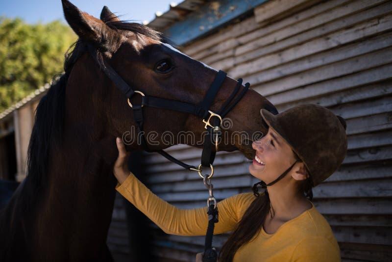 Lycklig kvinnlig jockey som slår hästen royaltyfria foton