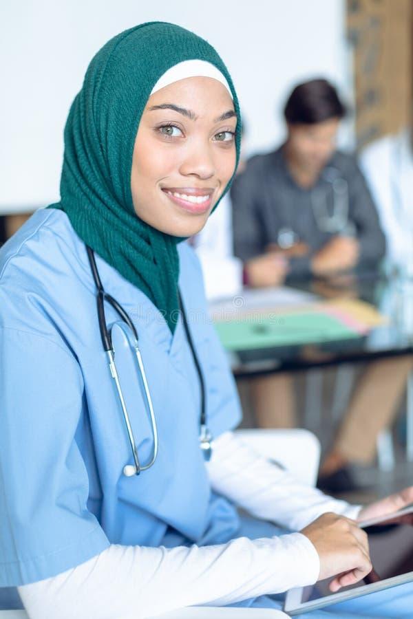 Lycklig kvinnlig kirurg i hijab som ser kameran, medan genom att använda den digitala minnestavlan i sjukhuset arkivbild