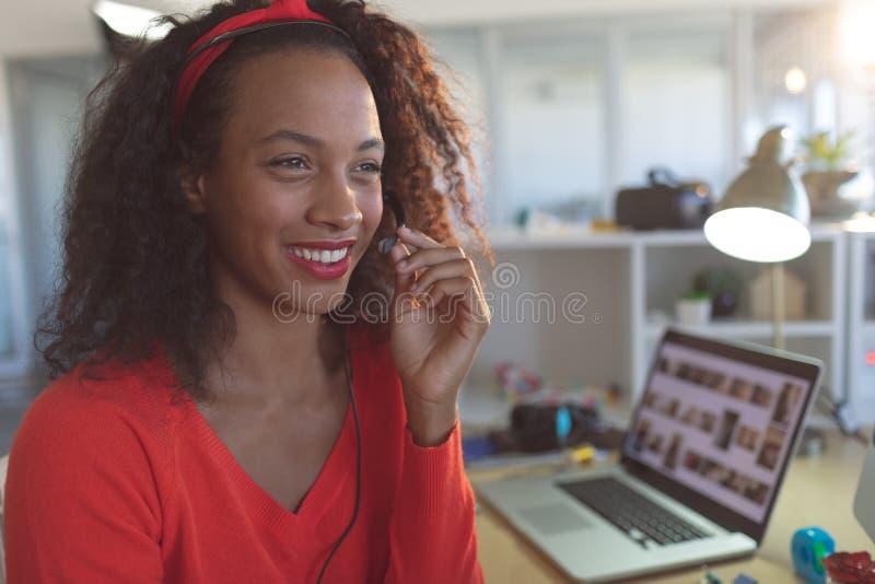Lycklig kvinnlig ledare som talar på hörlurar med mikrofon på skrivbordet fotografering för bildbyråer