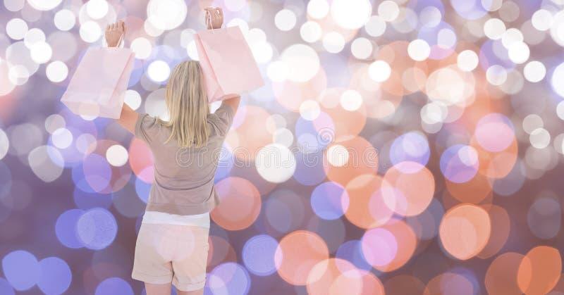 Lycklig kvinnlig med shoppingpåsar över bokeh fotografering för bildbyråer
