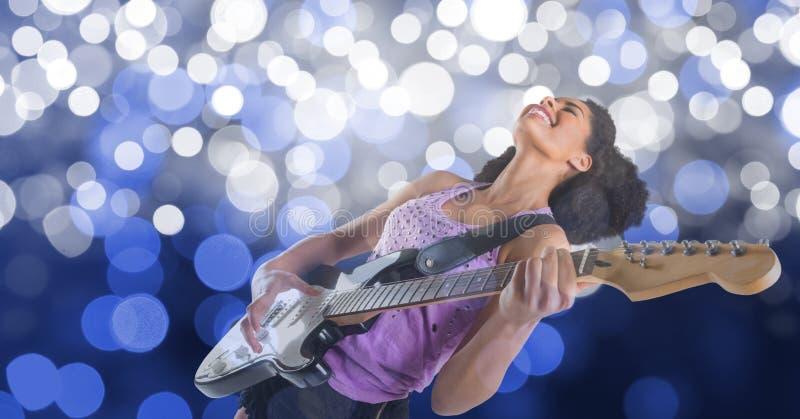 Lycklig kvinnlig musikkonstnär som spelar gitarren över bokeh royaltyfri fotografi