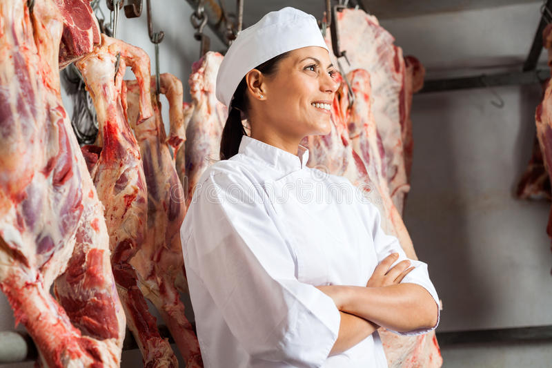 Lycklig kvinnlig slaktare Standing In Slaughterhouse royaltyfri fotografi