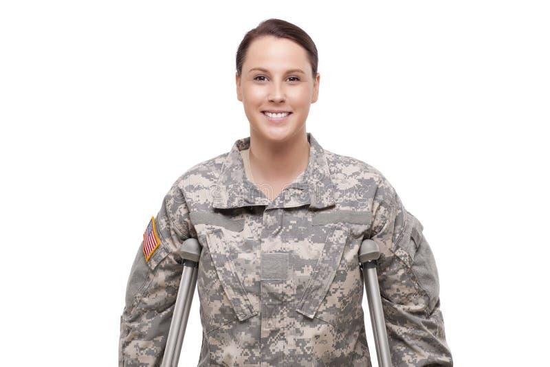 Lycklig kvinnlig soldat med kryckor arkivfoto