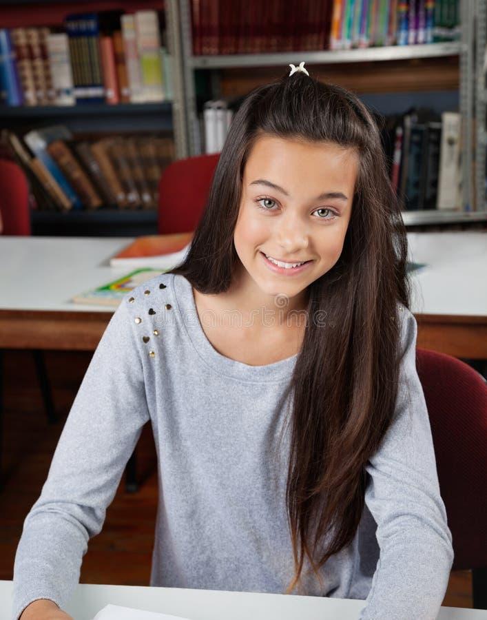Lycklig kvinnlig student Sitting In Library arkivbild