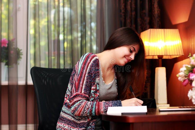 Lycklig kvinnlig student som gör läxa fotografering för bildbyråer