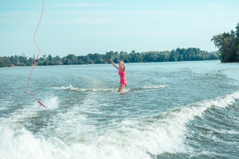 Lycklig kvinnlig wakeboarder som knee-deep står i vattnet royaltyfria foton